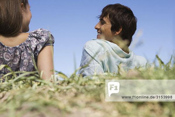 Junges paar entspannenden im Gras  Rückansicht