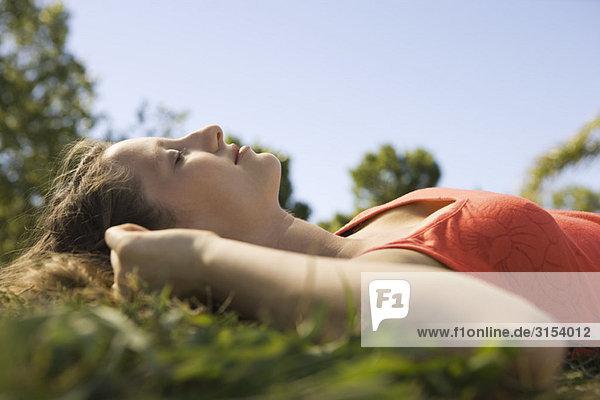 Junge Frau im Gras mit geschlossenen Augen liegen