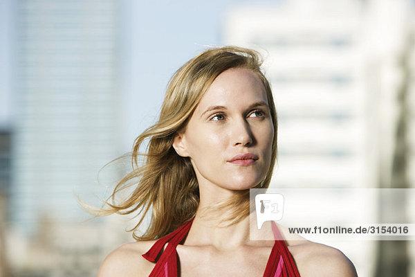 Junge Frau im Freien  auf der Suche entfernt in dachte  Haar zerzaust von breeze