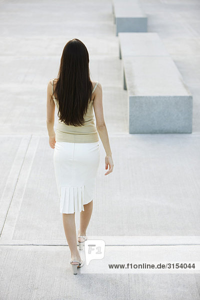 Woman walking in city square  rear view