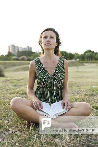 Frau sitzt auf Gras  Buch