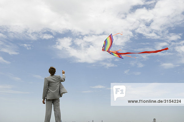 Kaufmann flying Kite in Feld  Rückansicht