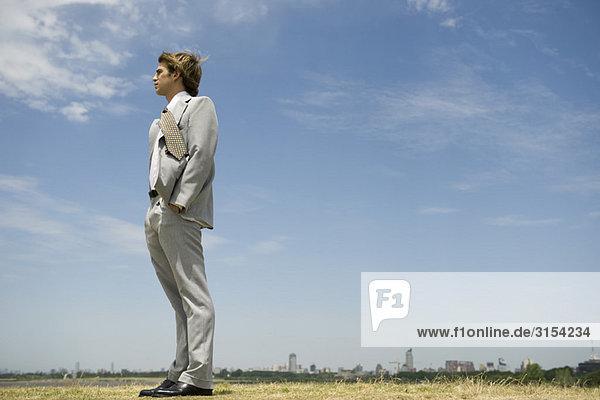 Kaufmann mit Händen in Taschen im Freiland  Skyline der Stadt auf fernen Horizont