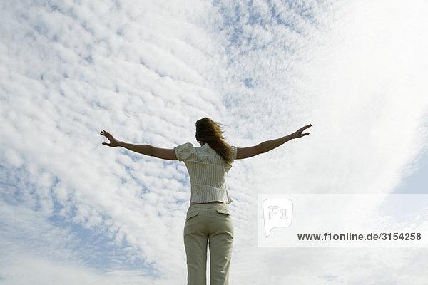 Frau mit Arms ausgestreckt  bewölkten Himmel im Hintergrund  Rückansicht