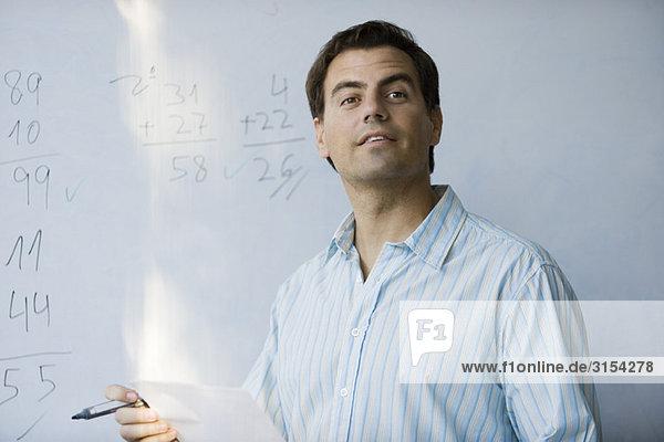 Mathelehrer vor dem Whiteboard  erwartungsvoll schauend