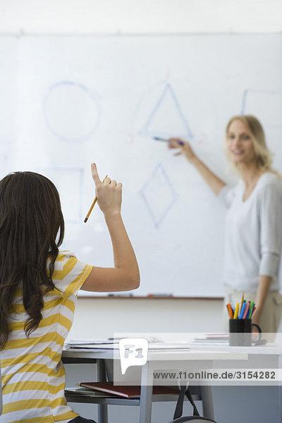 Gymnasiast hebt die Hand und beantwortet die Frage des Lehrers.