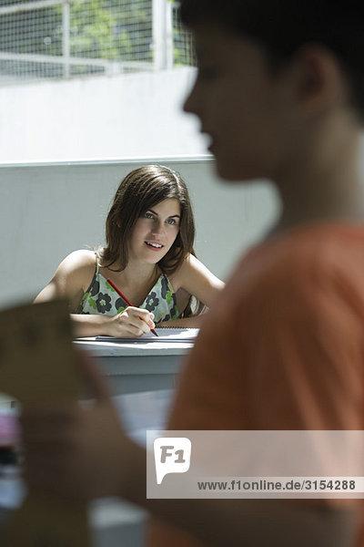 Teenager Mädchen macht Hausaufgaben  Junge im Vordergrund