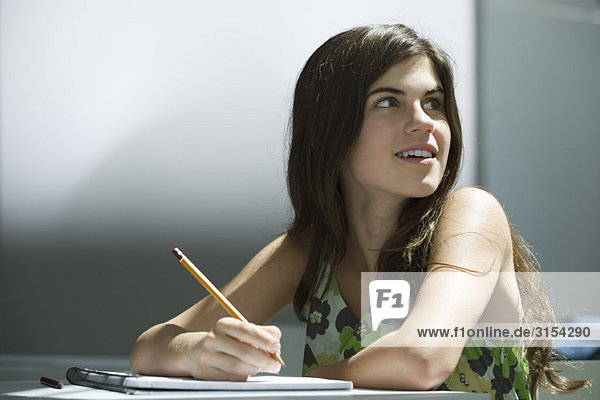 Teenager-Mädchen beim Schreiben im Notizbuch  verträumt wegschauen