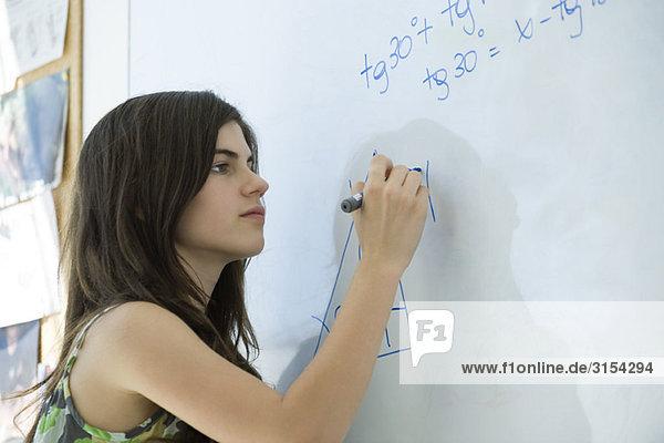 High-School-Schüler schreiben Gleichung auf Whiteboard