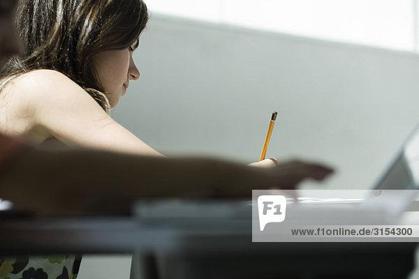 Teenager-Mädchen beim Schreiben am Schreibtisch