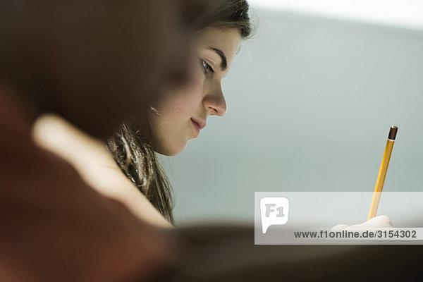 Teenage Girl beim Schreiben in der Klasse  Seitenansicht