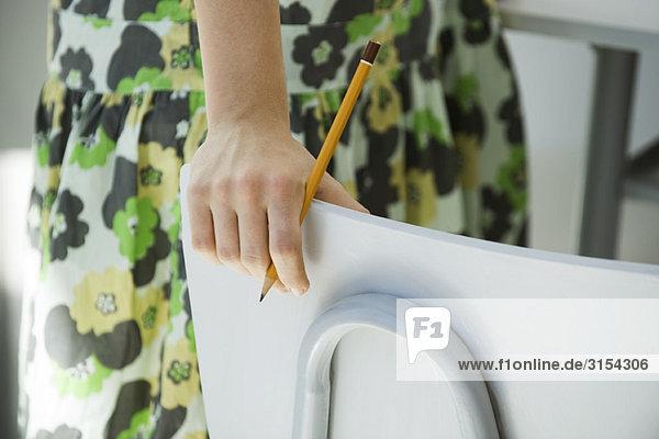 Frau neben Stuhl stehend  Bleistift in der Hand  beschnitten