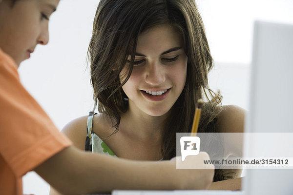 Tutorin hilft Grundschülerin bei den Hausaufgaben