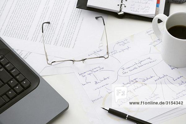 Handschriftlicher Businessplan auf überladenem Schreibtisch