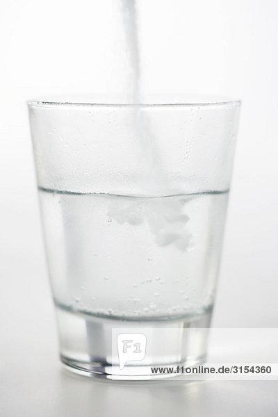 Gießen von Medikamentenpulver in ein Glas Wasser