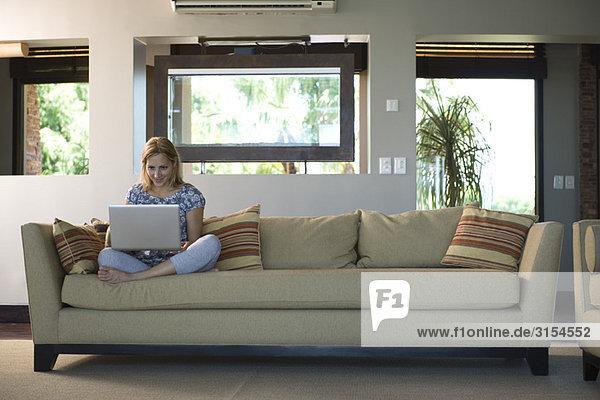 Junge Frau auf dem Sofa sitzend mit dem Laptop