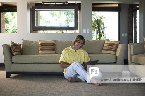 Mann sitzt auf dem Boden des Wohnzimmers mit dem Laptop