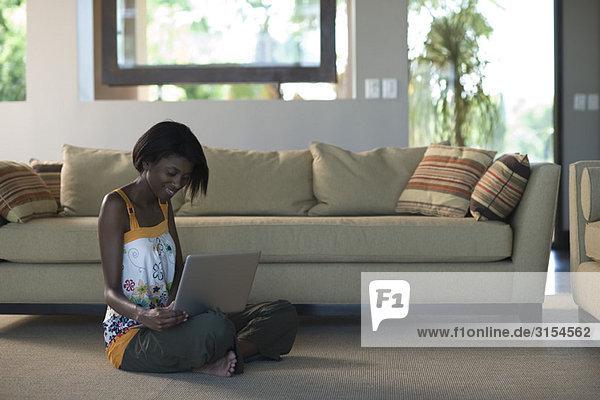 Junge Frau sitzt auf dem Boden des Wohnzimmers mit dem Laptop