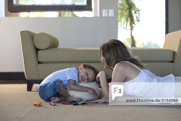 Mutter und Sohn zusammen im Wohnzimmer spielen  Junge umarmend Plüschtier