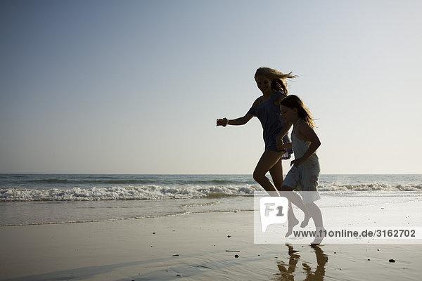 Eine Mutter und Tochter wird übersprungen unten am Strand