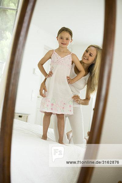 Eine Mutter und Tochter suchen in einem Spiegel