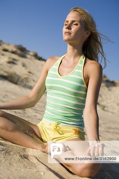 A woman doing yoga at the beach
