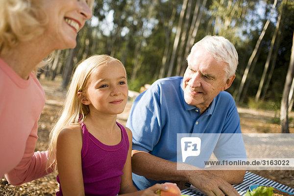Großeltern und Enkelin bei einem Picknick