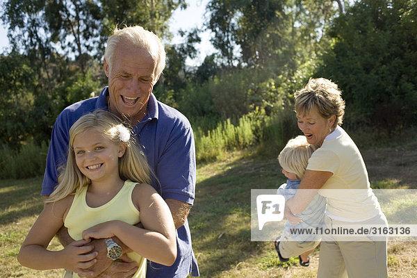 Großeltern und Enkel spielen in einem park