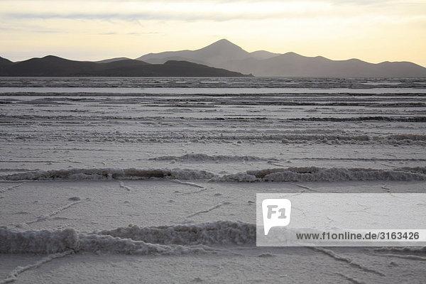 Zu Wellen erstarrtes Salz des Salar de Uyuni mit fernem Gebirge und Abendlicht im Hintergrund