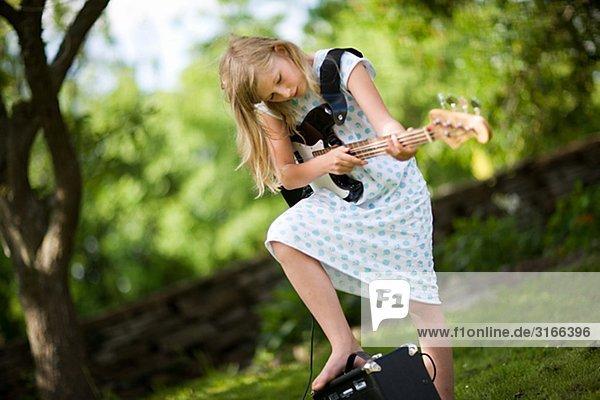 A Scandinavian girl playing the electric bass guitar Sweden.