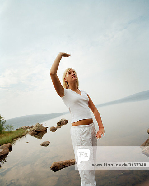 Junge Frau üben Yoga an einem See  Schweden.