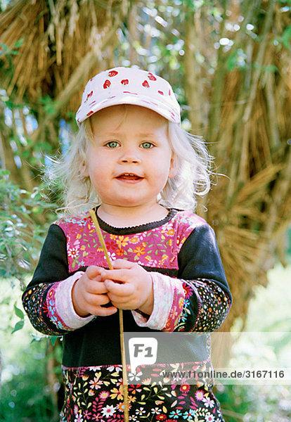 Portrait eines kleinen Mädchens an einem Busch  Schweden.