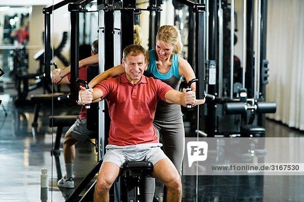 Ein Mann und eine Frau Krafttraining in einem Fitnessstudio Schweden.