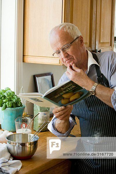 Senior man about to cook reading a cookbook  Sweden.
