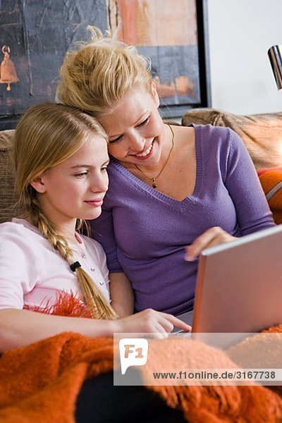 Mother and daughter using a laptop in a couch  Sweden.