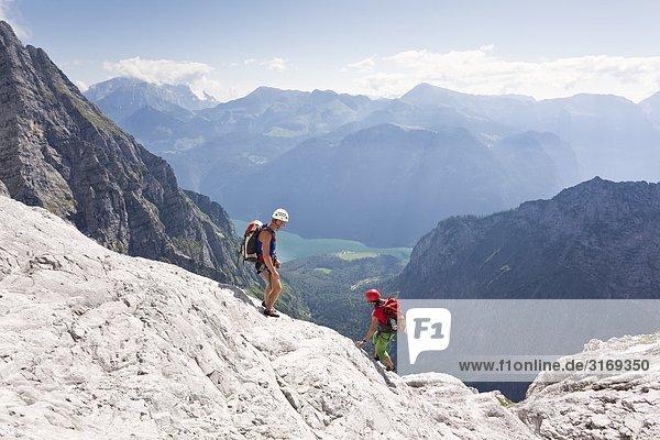 Paar auf einem Felsen in den Berchtesgadener Alpen  Königssee im Hintergrund  Bayern  Deutschland