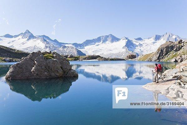 Frau an einem Bergsee  Zillertaler Alpen im Hintergrund  Tirol  Österreich  Seitenansicht