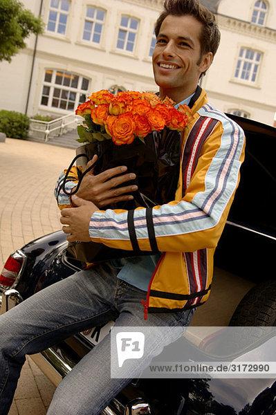 Junger Mann wartet sitzend auf dem Kofferraum eines Autos mit einem Blumenstrauß - Strasse