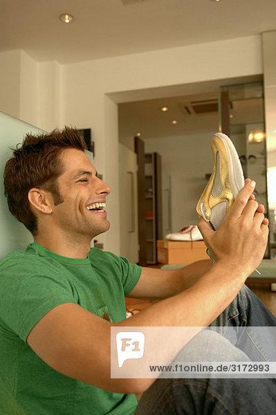 Junger dunkelhaariger Mann freut sich über den Schuh in seiner Hand - Geschäft - Laden