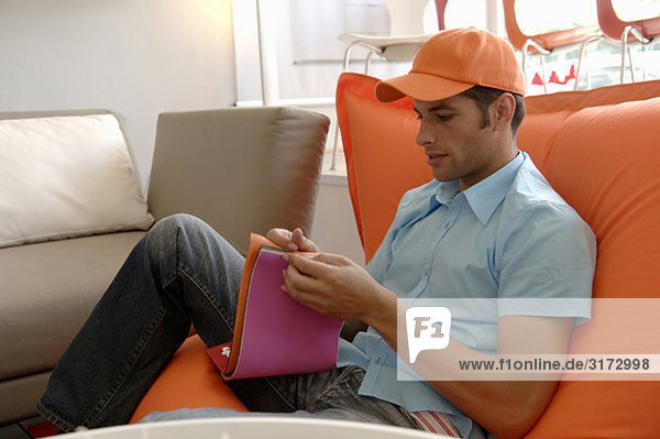 Junger Mann mit oranger Mütze sitzt auf einer Couch und sucht ein Farbe aus - Geschäft - Laden
