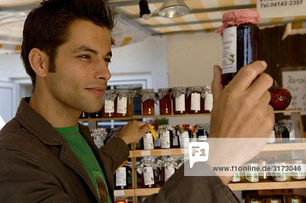 Junger schwarzhaariger Mann begutachtet ein Marmeladenglas - Regal - Geschäft - Laden