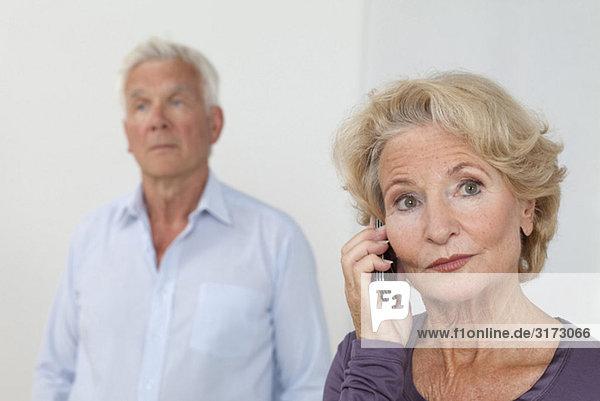 Seniorin telefoniert mit Mann im Hintergrund Seniorin telefoniert mit Mann im Hintergrund