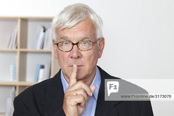 Senior man putting finger on lips