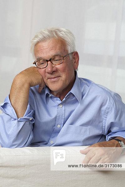 Zufriedener Senior mit Brille sitzt auf der Couch