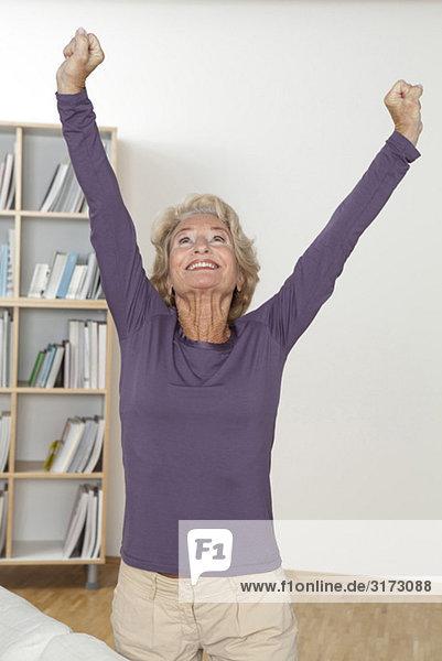 Jubelnde Seniorin mit erhobenen Armen
