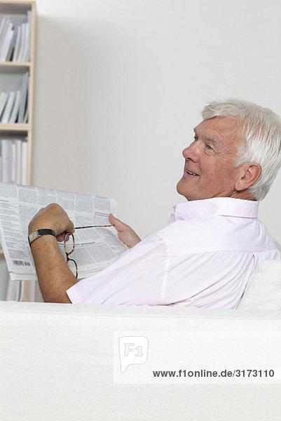 Senior liest Zeitung auf der Couch Senior liest Zeitung auf der Couch