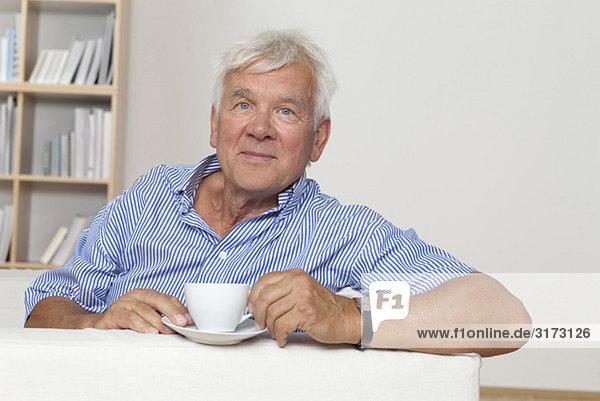 Entspannter Senior mit einer Tasse Kaffee auf der Couch Entspannter Senior mit einer Tasse Kaffee auf der Couch