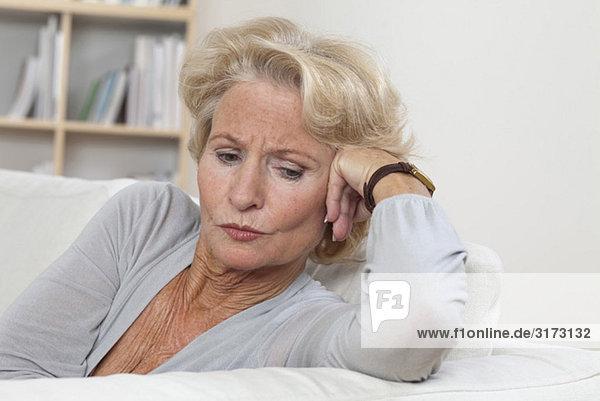 Nachdenkliche Seniorin auf der Couch