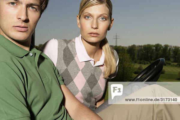Junges Paar in einem Golfwagen