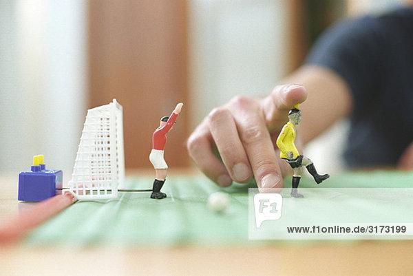 Mann spielt mit Tischfussballspiel (Detail)